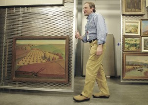 "Andrew Wallace, registrar for the Figge Art Museum in Davenport, slides the rack containing Grant Wood's ""Fall Plowing"" back into storage, Wednesday Dec. 23, 2009. The painting will be the key piece in a permanent exhibit at the Figge. (John Schultz / Quad-City Times)"